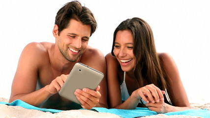 Couple relaxing on the beach with a tablet