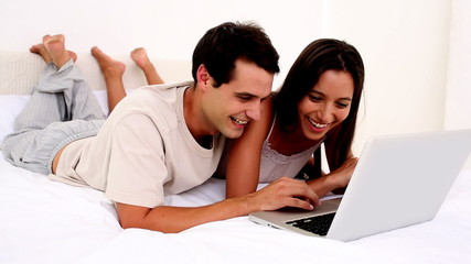 Delighted couple using a laptop