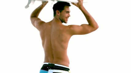 Attractive man holding a surfboard above his head