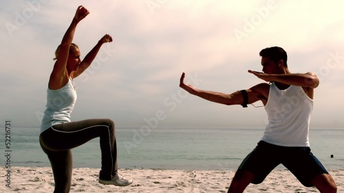 Athletes doing martial arts on the beach