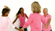 Women dancing in a circle and holding hands wearing pink for breast cancer