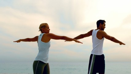 Man and woman doing pilates on beach