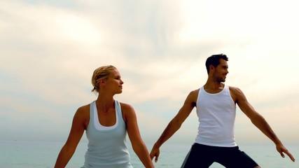 Man and woman doing yoga on beach together