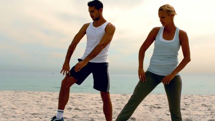 Man and woman doing pilates on beach together