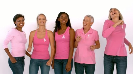 Women wearing pink ribbon against cancer dancing