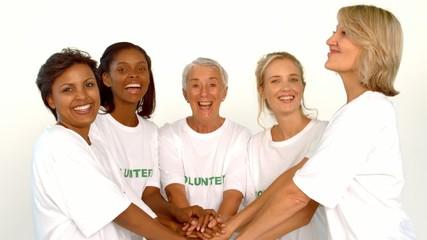 Volunteers raising hands together