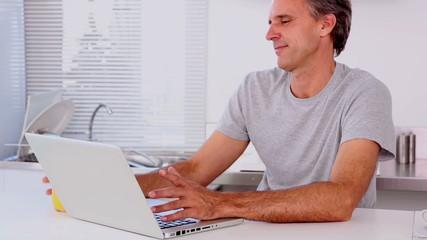 Mature man drinking orange juice while using his laptop
