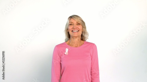 Cheerful women hiding behind another woman wearing breast cancer ribbon