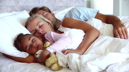 Parents and daughter holding teddy bear sleeping peacefully