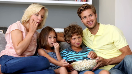 Family eating popcorn and watching tv together