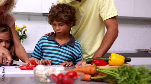 Mother showing her daughter how to chop vegetables with her family