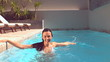Happy woman standing and splashing in pool