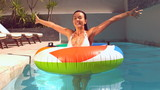 Pretty woman emerging from underwater into rubber ring in pool