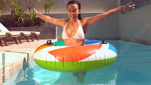 Happy woman emerging from underwater into rubber ring in pool
