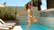 Attractive brunette plunging into swimming pool