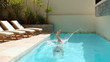 Attractive woman diving into swimming pool