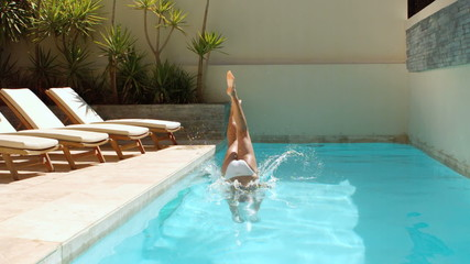 Attractive brunette diving into swimming pool