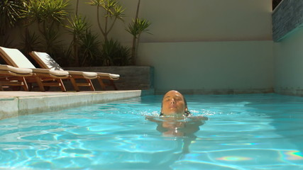Attractive woman immersing her head in swimming pool