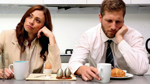 Distant couple having breakfast and not talking