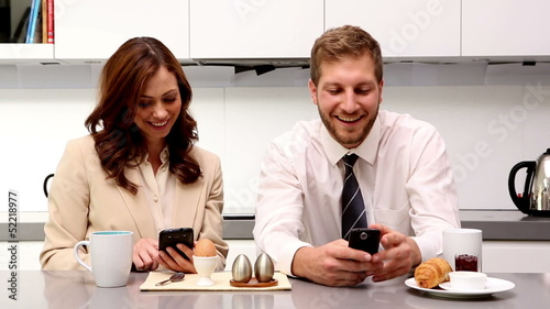 Couple showing each other their phones at breakfast