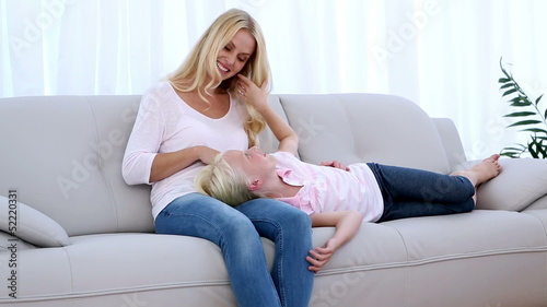 Daughter resting on mothers lap and playing with her hair