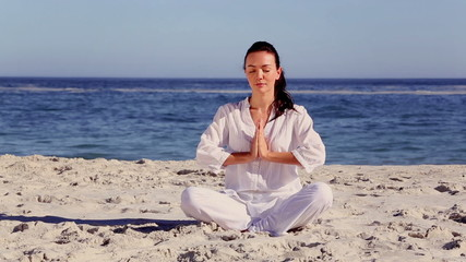 Brunette woman meditating in sukhasana pose