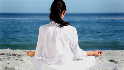 Brunette woman meditating in sukhasana pose rear view