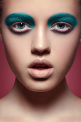 Girl with bright aquamarine eye make-up, full lips, clean skin