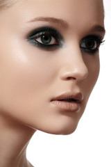 Face with dark green smoky-eyes make-up, pale full lips