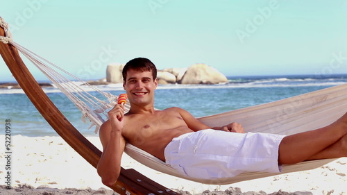 Attractive man eating ice lolly in a hammock