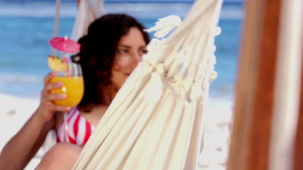 Pretty girl in a hammock raising her cocktail glass