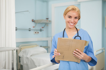 Nurse smiling at camera while holding a folder