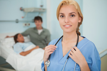 Blonde nurse looking at camera next to a patient
