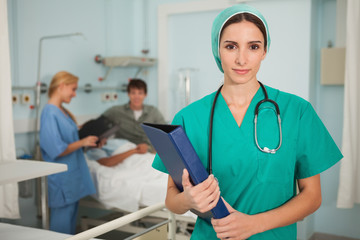 Nurse looking at camera while holding a binder