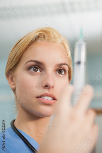 Focus on a nurse looking at a syringe