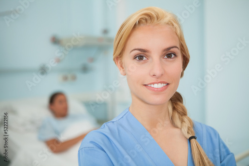 Close up of a blonde nurse looking at camera
