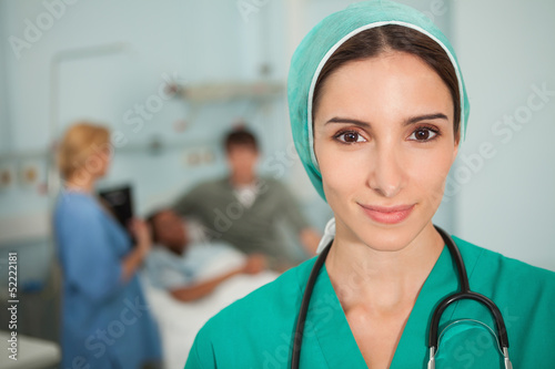 Nurse looking at camera next to a medical bed