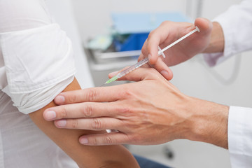 Close up of a doctor doing an injection to the patient arm