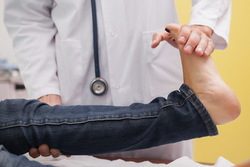 Doctor auscultating a patient ankle