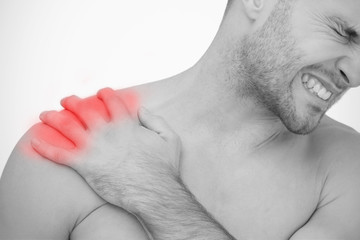 Man wincing in pain at sore shoulder