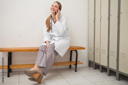 Smiling doctor sitting on a bench while calling