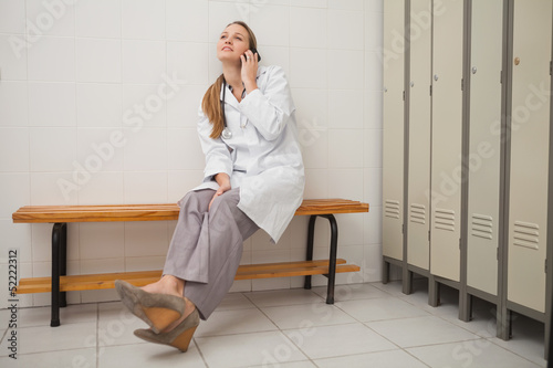 Doctor sitting on a bench while calling