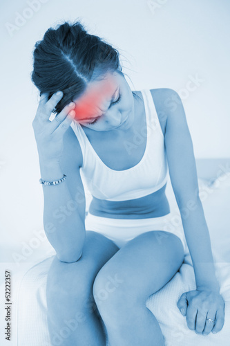 Woman rubbing her head with highlighted red pain