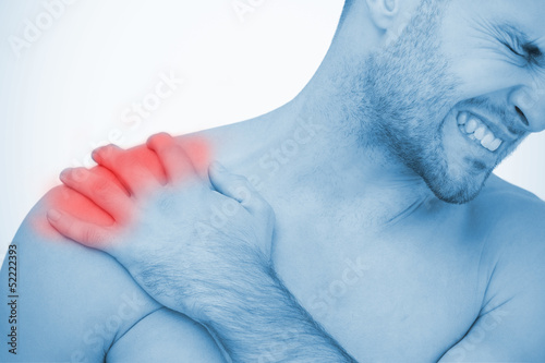 Man wincing in pain at shoulder pain