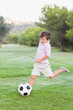 Little boy kicking football