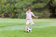 Little boy kicking his football