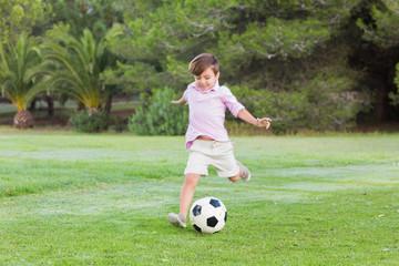 Little boy kicking his football