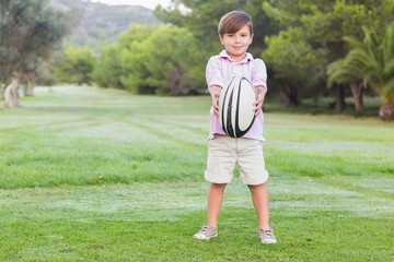 Smiling boy holding out rugby ball