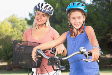 Portrait of mother and daughter with bikes