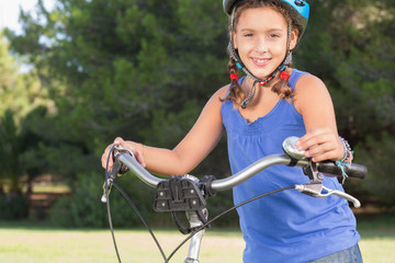 Happy girl standing with bicycle